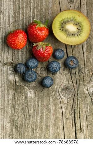 Top view on fresh strawberries, blueberries and kiwi on white table - stock photo