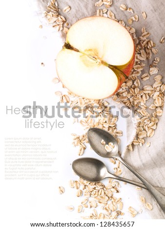 Top view on half apple with crops oatmeal and vintage spoons on textile over white with sample text - stock photo