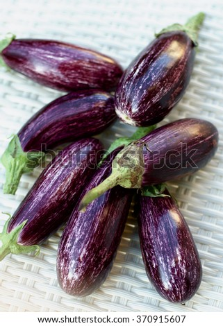 Top View on Heap of Fresh Raw Striped Eggplants closeup on Wicker background. Selective Focus - stock photo