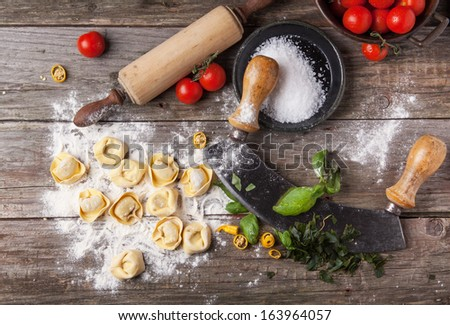 Top view on homemade pasta ravioli on old wooden table with flour, basil, tomatoes and vintage kitchen accessories - stock photo