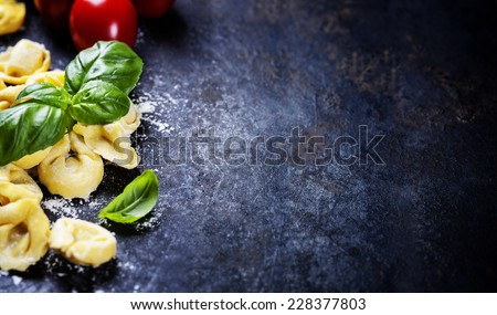 Top view on homemade pasta ravioli  with flour, tomato  and basil on dark vintage background - stock photo