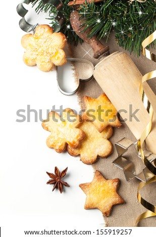 Top view on homemade sugar cookies served with metal cookie cutters and wooden rolling pin near christmas tree over white - stock photo
