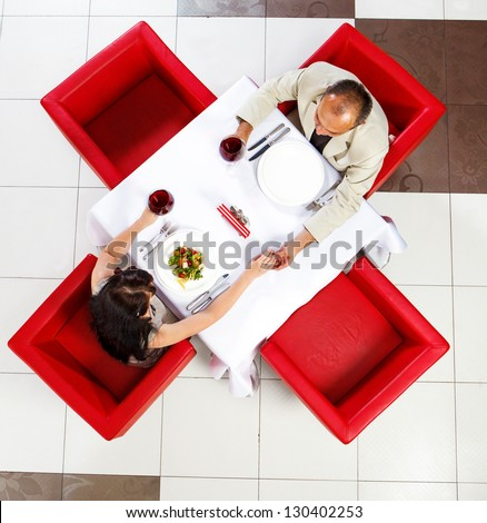 Top view on middle aged man and woman holding hands in a restaurant - stock photo