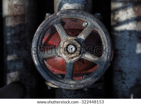 top view on old handwheel of valve in a dark background - stock photo