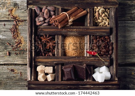 Top view on old wooden box with set of coffee and cocoa beans, sugar cubes, dark chocolate, cinnamon and anise over wooden background - stock photo