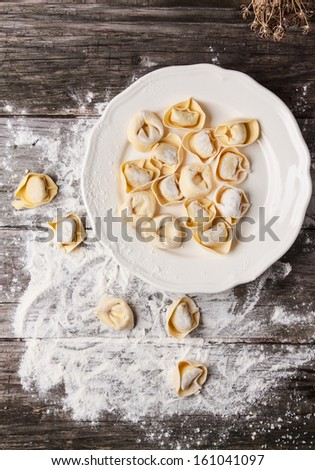 Top view on plate of homemade pasta ravioli over wooden table with flour - stock photo