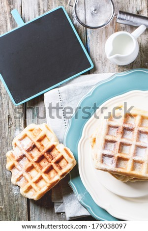 Top view on plates with fresh belgian waffles served with empty black chalkboard over old wooden table. See series - stock photo