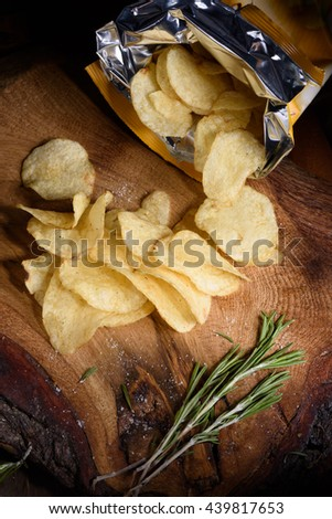 Top view on potato chips with fresh rosemary on wooden board. Open bag of salty snack. - stock photo