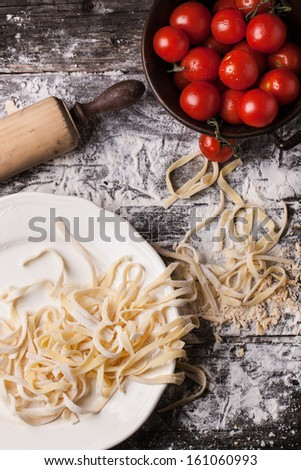 Top view on Raw homemade pasta with tomatoes and flour over old wooden table - stock photo