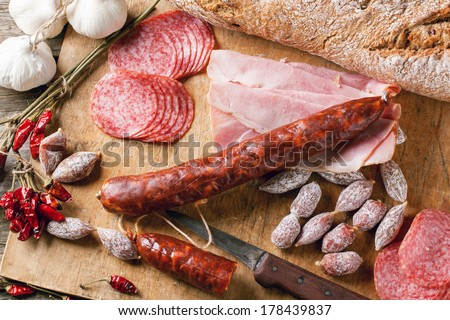 Top view on set of ham and salami served with red hot chili peppers on wooden cutting board. See series. - stock photo