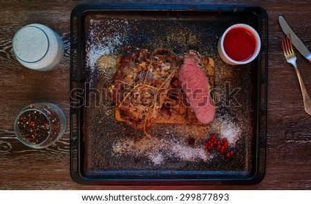 Top view on the table is a pan which is a large piece of mutton, standing next sousostry with the addition of sour grapes - stock photo