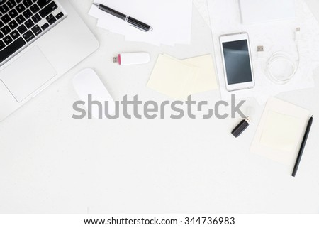 Top view on working desk with laptop and office equipment with blank space - stock photo