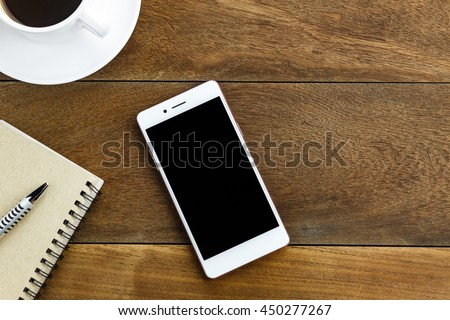Top view pen,note paper,cup of coffee,smartphone or mobile phone by business or technology background with copy space. - stock photo