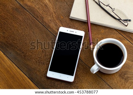 Top view pen,note paper,cup of coffee,smartphone or mobile phone,eyeglasses by business or technology background. - stock photo