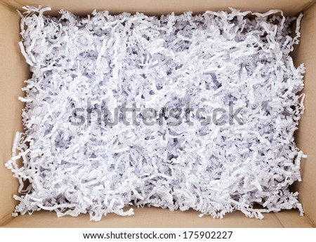 Top view photo of an open mail parcel with wrinkled white padding paper of filling inside it. - stock photo