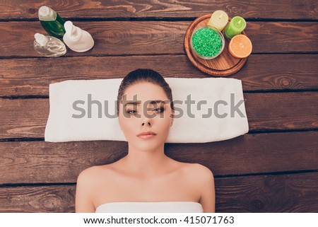 Top view photo of attractive young girl relaxing in spa salon with spa cosmetics - stock photo