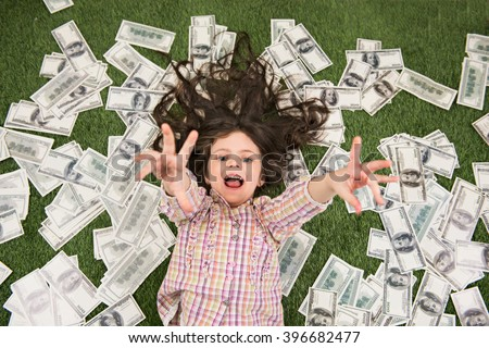 Top view photo of beautiful little girl lying on green grass and dollars. Girl reaching hands to camera - stock photo