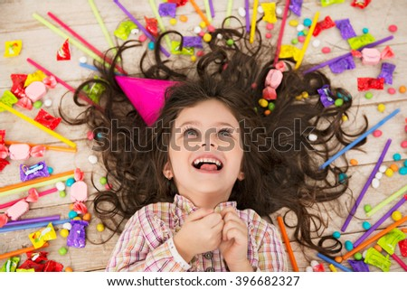 Top view photo of beautiful little girl lying on wooden floor with candies. Girl wearing birthday hat and cheerfully smiling - stock photo