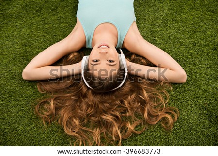 Top view photo of beautiful young woman lying on green grass. Woman listening to music with headphones and looking at camera - stock photo