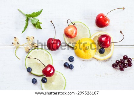 Top view photo of lemon, lime, cherry, red and white currant and blueberries on white wooden table. Summer snack concept with green mint leaves. - stock photo