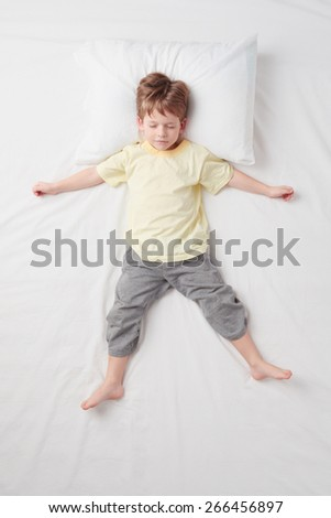 Top view photo of little cute boy sleeping on white bed. Quiet Star pose. Concept of sleeping poses - stock photo