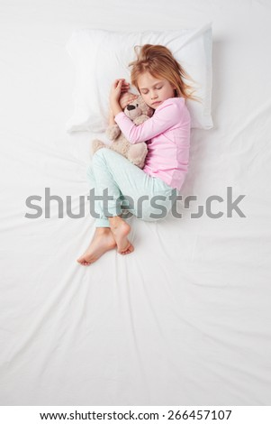 Top view photo of little girl sleeping on white bed with teddy bear. Quiet Foetus pose. Concept of sleeping poses - stock photo