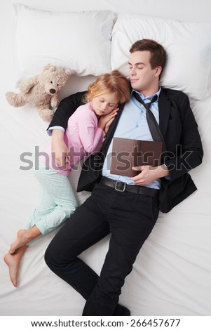Top view photo of tired businessman wearing suit, with open book and his little cute daughter. Father's arm is over daughter. They both sleeping on white bed - stock photo