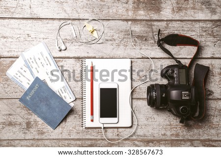 Top view photo of white mobile phone, professional camera, notebook, passport, tickets, pencil, origami bird and headphones. Objects are on light colored wooden floor - stock photo