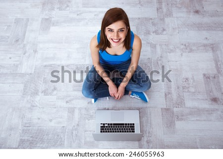 Top view portrait of a happy woman sitting at the floor with laptop - stock photo