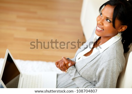 Top view portrait of a pretty woman sitting at home on the floor in front her laptop while is looking up - stock photo