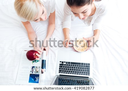 Top view portrait of a two women lying on the bed and using laptop computer - stock photo