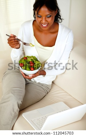 Top view portrait of an adult woman eating healthy green salad while is sitting on sofa in front of her laptop - stock photo