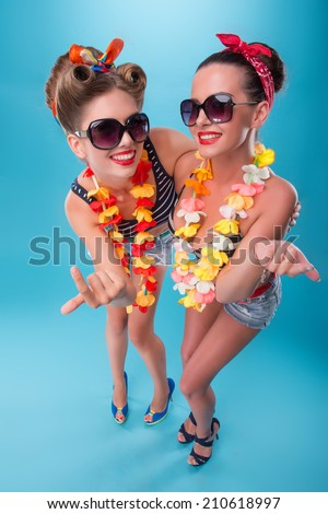 Top view portrait of two beautiful emotional coquette sexy girls with pretty smiles in pinup style with Hawaiian flowers necklaces, inviting somebody with finger isolated on blue - stock photo