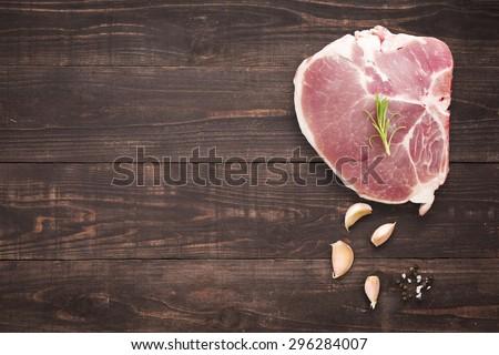 Top view raw pork chop steak and garlic, pepper on wooden background. - stock photo