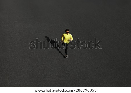 Top view runner man running sprinting for success on run at black road in yellow sportswear. Muscular fit sport model sprinter exercising sprint on city road. Full body length of Caucasian model.  - stock photo