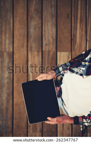 Top view shot of a woman holding digital tablet with a blank screen- closeup, fem a hands holding blank digital tablet against beautiful wooden copy space area, filtered image  - stock photo