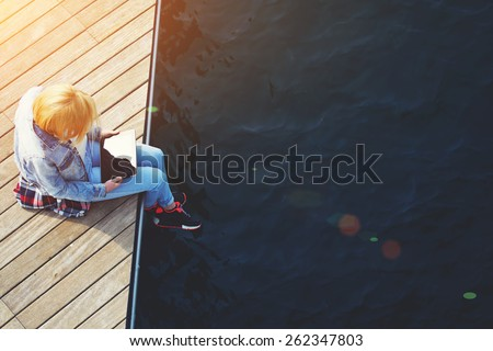 Top view shot of a young blonde hair woman sitting on a jetty next to a sea while using busy digital tablet with a blank screen, tourist woman searching information on tablet while relaxing on a pier - stock photo