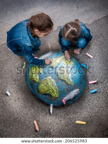 Top view shot of two girls drawing realistic Earth image with chalks on ground - stock photo