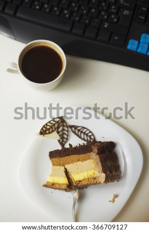 Top view slice of cake on plate, cup of coffee and keyboard on table - stock photo