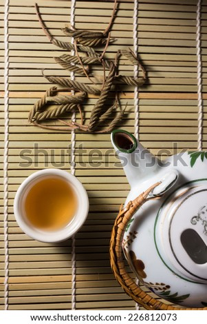Top view tea set with leaves on bamboo mat.  - stock photo