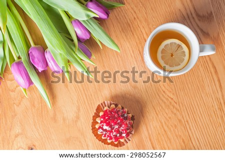 Top view to the fresh violet tulips, cake and tea on the wooden table - stock photo