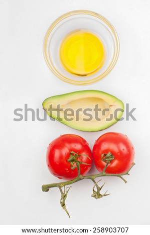 Top view to the tomatoes, avocado and olive oil - stock photo