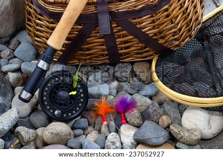 Top view up of  fishing fly reel, landing net, creel and assorted flies on dry river bed rocks  - stock photo