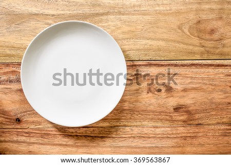 Top view white Empty plate on old wooden background. - stock photo