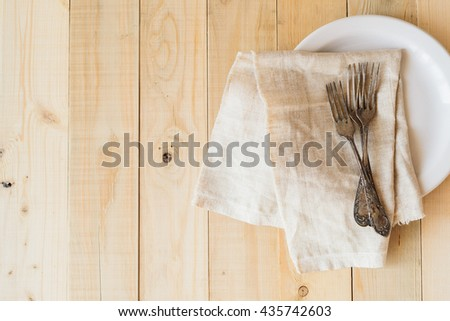 Top view wooden table setting with copyspace, three antique forks and linen napkin on white plate - stock photo