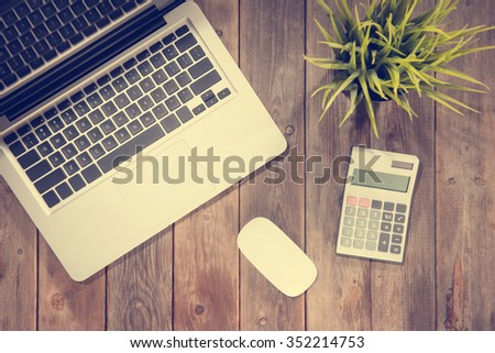 Top view working desk with laptop computer, calculator and plant pot. Wooden table background with copy space in vintage toned. - stock photo