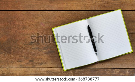 Top view workspace with blank notebook and pen on wooden table background . - stock photo