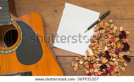 Top view workspace with blank paper ,acoustic guitar and dried flowers on wooden table background. - stock photo
