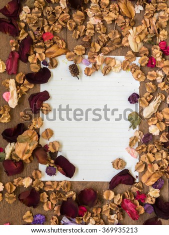 Top view workspace with blank paper and dried flowers on wooden table background . - stock photo