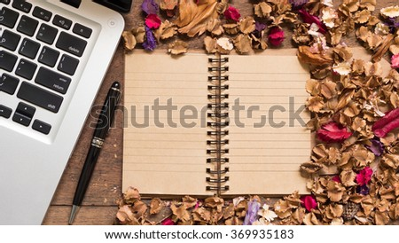 Top view workspace with notebook,pen,laptop and dried flowers on wooden table background . - stock photo